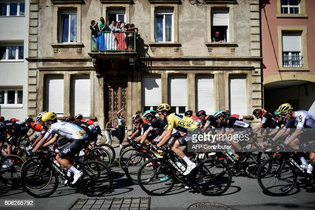 TOPSHOT Great Britain's Geraint Thomas wearing the overall leader's yellow jersey rides in the pack past supporters during the 2125 km third stage of...