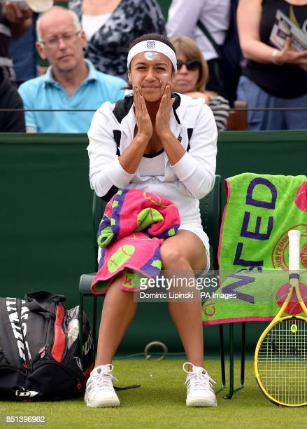 Great Britain's Heather Watson applies sun cream to her face ahead of her double's match during day Three of the Wimbledon Championships at The All...