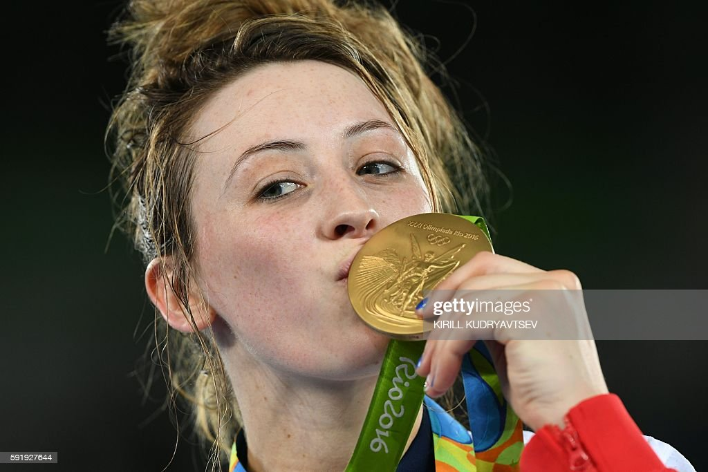 Great Britain's Jade Jones poses with her gold medal on the podium after the womens taekwondo event in the -57kg category as part of the Rio 2016 Olympic Games, on August 18, 2016, at the Carioca Arena 3, in Rio de Janeiro. / AFP / Kirill KUDRYAVTSEV