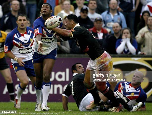 Great Britain's Leon Pryce offload under pressure from New Zealand's David Kidwell during the XXXX Test at Knowsley Road St Helens