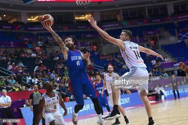 Great Britain's Luke Nelson tries to score next to Belgium`s Maxime de Zeeuw and Jonathan Tabu during the FIBA Eurobasket 2017 men`s group D...