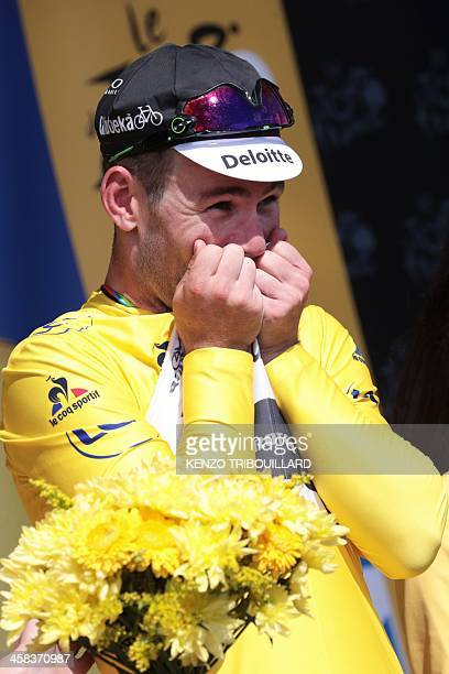 Great Britain's Mark Cavendish celebrates his overall leader yellow jersey on the podium at the end of the 188 km first stage of the 103rd edition of...