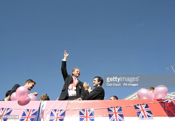 Great Britain's Olympic Rower Matt Wells of the Mens Double Scull team waves as they ride on an opentop bus during an Olympic Rowing Heroes Return...