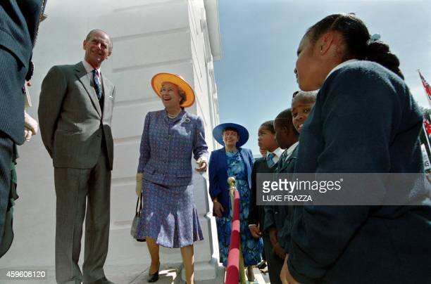 Great Britain's Queen Elizabeth II and Prince Philip chat with school children outside city hall where the Queen unveiled a plaque for a time capsule...