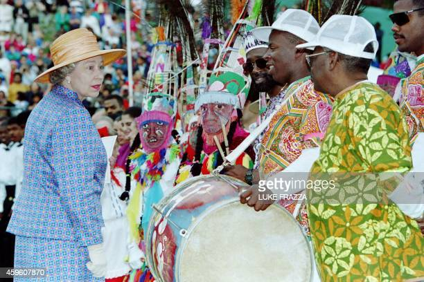 Great Britain's Queen Elizabeth II chats with members of the H and N Gombeys a native Bermudian dance troop on March 8 1994 at the Botanical Garden...