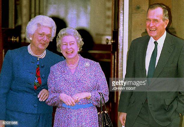 Great Britain's Queen Elizabeth II shares a joke with former president George Bush and wife Barbara 30 November 1993 after he was awarded an honorary...