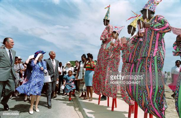 Great Britain's Queen Elizabeth II watches local Anguillan boys on stilts line up in a street moments after she inaugurated an avenue in her honour...