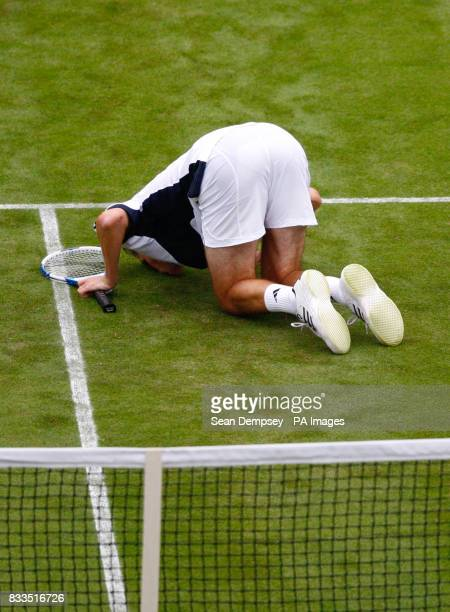 Great Britain's Tim Henman kisses the court after his victory over Croatia's Roko Karanusic during the first day at the All England Club Wimbledon