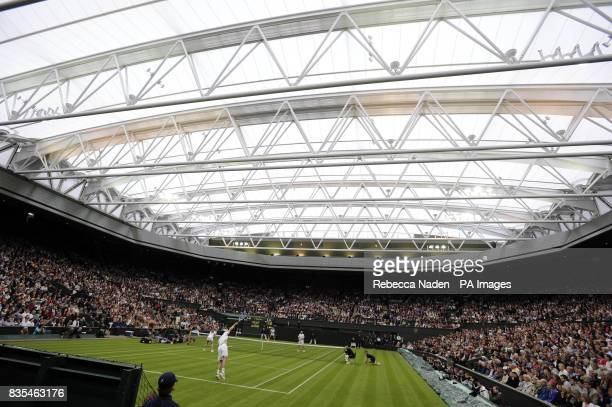 Great Britain's Tim Henman serving on centre court with his partner Kim Clijsters against Andre Agassi and wife Steffi Graf during the Centre Court...