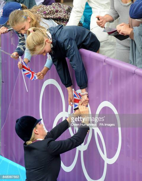 Great Britain's Zara Phillips signs autographs after winning a silver medal in the Team Eventing on day four of the London Olympic Games at Greenwich...