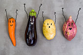 Great concept of healthy eating, vegetables with happy faces with arms up, potato, sweet potato, carrot, eggplant. Gray background, polished concrete.
