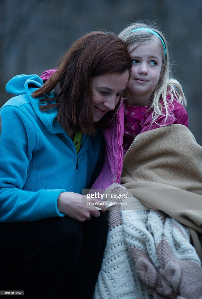 Great Falls Ecumenical Council's Easter sunrise service at 6:30 a.m. at Great Falls National Park. Jennifer Blackwell, of Ann Arbor, cuddles with her 6-year-old daughter, Penny Walke, during the service.