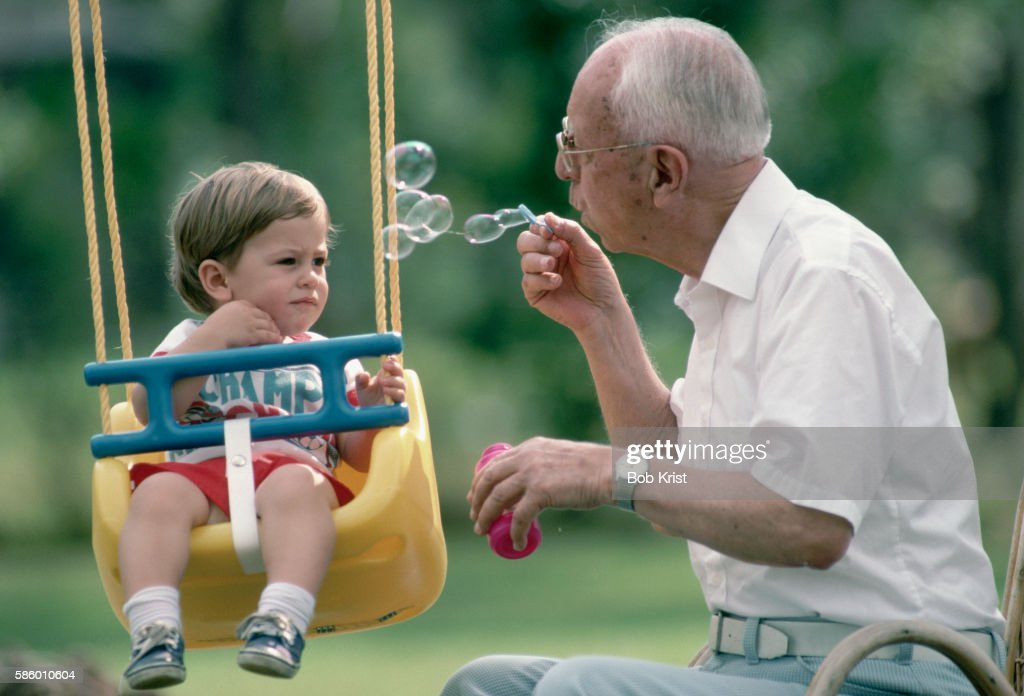 Great Grandfather Blowing Bubbles for His Great Grandson