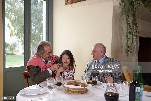 Great grandfather watching grandfather and granddaughter (5-7) at dinner table
