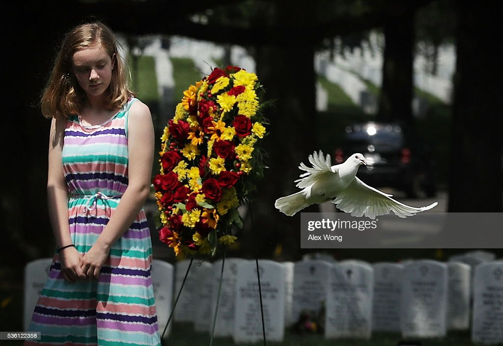 Great grandniece Madeline Brumbaugh of Springfield, Virginia, watches a dove flying away as the bird is being released during the burial of Private First Class James Bernard Johnson May 31, 2016 at Arlington National Cemetery in Arlington, Virginia. Johnson was assigned to Company K, 3rd Battalion, 8th Marines, 2nd Marine Division during WWII. He died sometime on the first day of battle against the Japanese, November 20, 1943, in an attempt to secure the small island of Betio in the Tarawa Atoll of the Gilbert Islands after landing.
