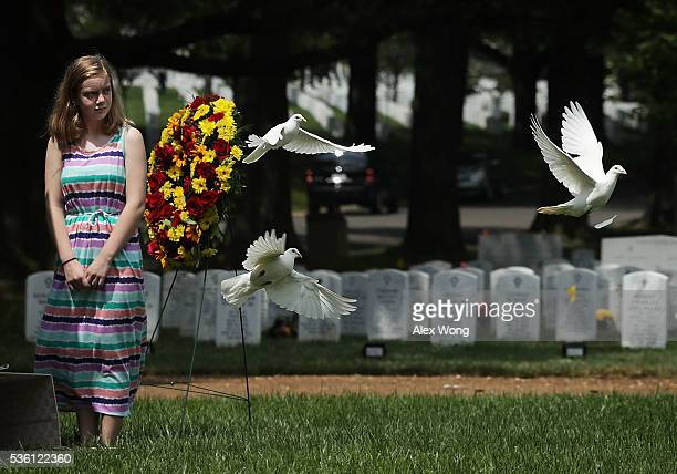 Great grandniece Madeline Brumbaugh of Springfield Virginia watches doves flying away as the birds are being released during the burial of Private...
