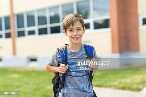 Great Portrait Of School Pupil Outside Classroom Carrying Bags : Stock Photo