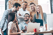 Group of six young people discuss something with smile while leaning to the table in office