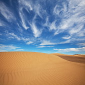 Great Sand Sea under blue sky .