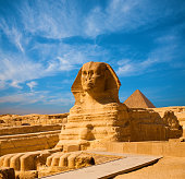 Full length body profile of Great Sphinx including head, feet with great pyramid of Menkaure in background on a clear, blue sky day in Giza, Egypt empty with no people. Copy space