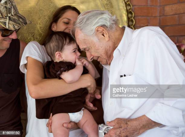 Great-grandfather nuzzling baby