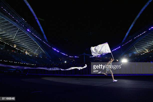 A runner carries an Athens summer games flag through the Olympic Stadium during the opening ceremony of the XXVIII Olympic Games 13 August 2004 in...