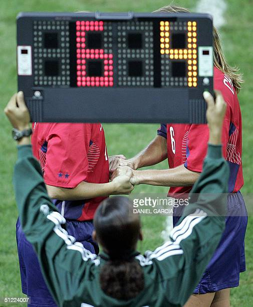 An assistant referee holds a board indicating the substitution of US defender Brandi Chastain Abby Wambach by US defender Cat Reddick during their...