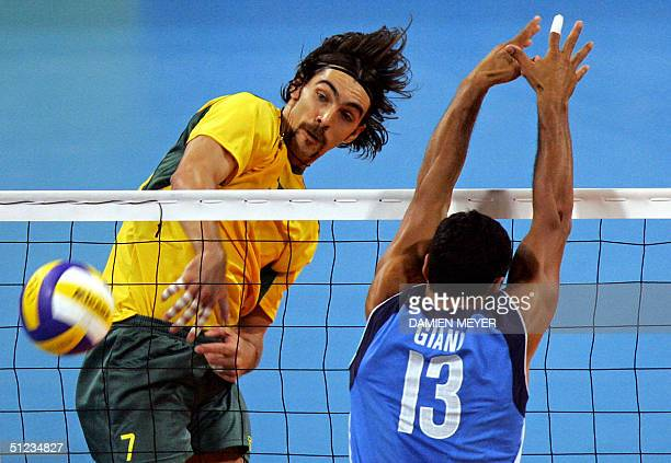 Brazilian best scorer Gilberto Godoy Filho spikes despite Italian captain Andrea Giani during their gold medal volleyball match at the Olympic Games...