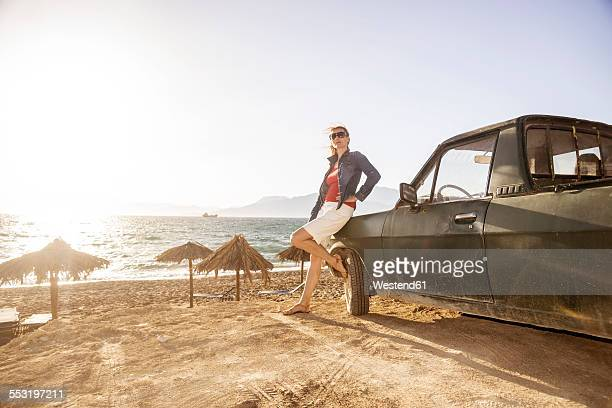 Greece, Crete, Matala, woman leaning against pickup truck at the beach