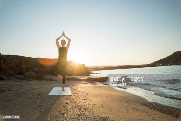 Greece, Crete, woman practicing yoga on the beach at sunset