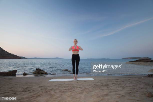 Greece, Crete, woman practicing yoga on the beach
