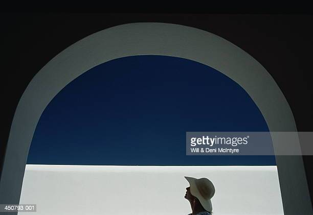 Greece, Cyclades Islands, woman standing under arch