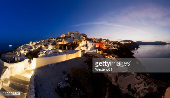 Greece, Cyclades, Thira, Santorini, Oia, View of blue dome and bell tower of a church with aegean sea at dusk