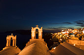 Greece, Cyclades, Thira, Santorini, View of bell tower and oia after sunset