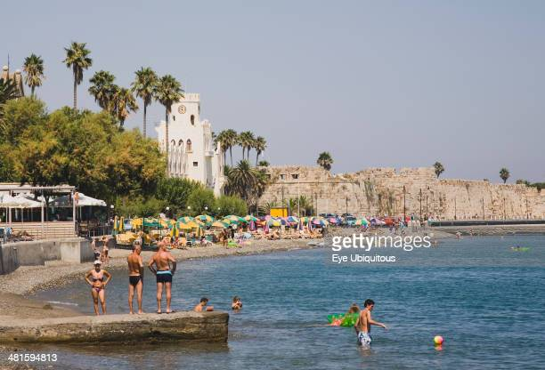 Greece Dodecanese Islands Kos Kos Town beach with castle walls and harbor entrance behind and Greek holidaymakers bathing on shingle beach in...