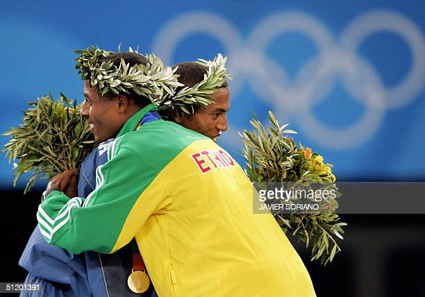 Ethiopia's Olympic 10000 gold medal winner Kenenisa Bekele hugs Eritrea's Zersenay Tadesse pose on the winners' podium 21 August 2004 during the...