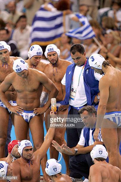 Greece' waterpolo players talk with their coach 21 August 2004 at the Olympic aquatic center at the 2004 Olympic Games in Athens AFP PHOTO GERARD...