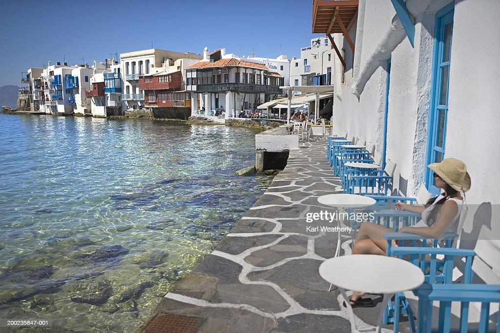 Greece, Mykonos, Little Venice, woman sitting near water