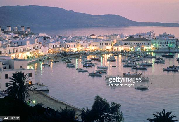Greece Mykonos Sunset Of Mykonos Harbor Lights In Buildings Boats Mountains In Background