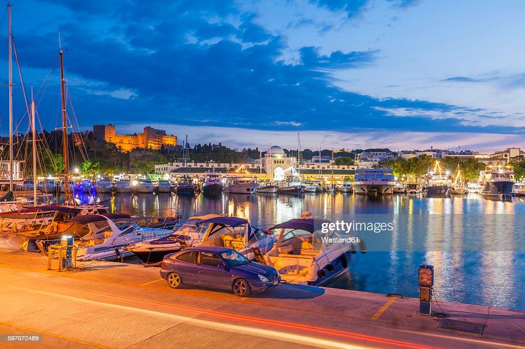 Greece, Rhodes, boats at Mandraki harbour at dusk