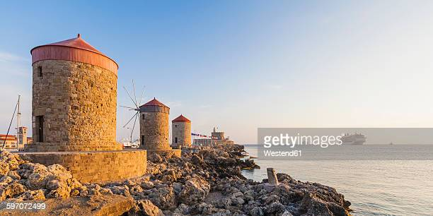 Greece, Rhodes, mole of Mandraki harbour with windmills and cruise ship in background