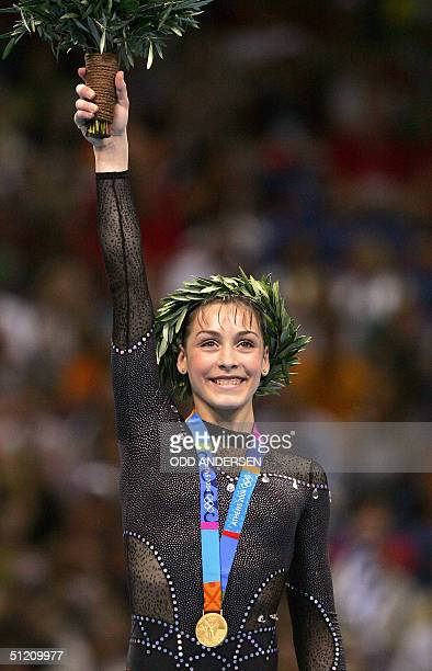 Romania's gold medallist Catalina Ponor smiles on the podium of the women's beam 23 August 2004 at the Olympic Indoor Hall in Athens during the...