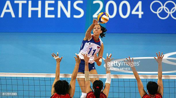Russian Ekaterina Gamova spikes against her Chinese opponents Wang Lina Liu Yanan and Yang Hao during the gold medal volleyball match between Russia...
