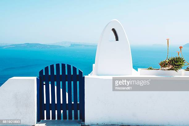 Greece, Santorini, Oia, gate and chimney in front of the sea