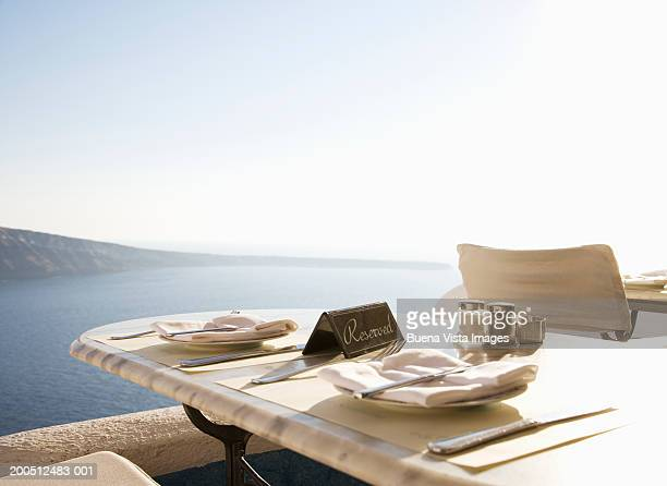 Greece, Santorini, Oia, reserved restaurant table overlooking sea