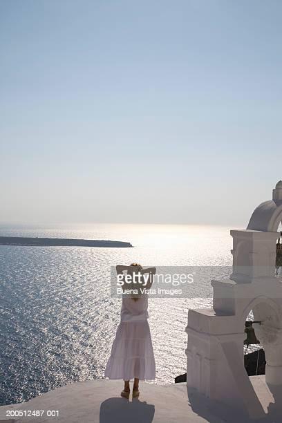 Greece, Santorini, Oia, woman facing sea, rear view, sunset