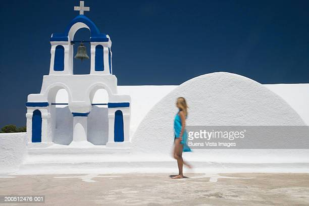 Greece, Santorini, Oia, woman passing church (blurred motion)