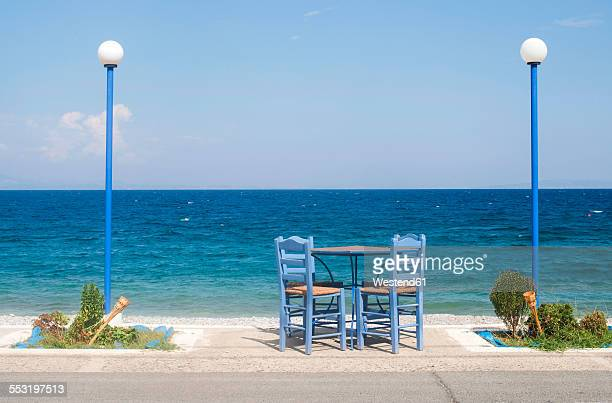 Greece, table and chairs of taverna at seashore