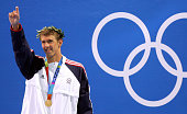 US Michael Phelps poses on the podium after winning the men's 100m butterfly gold medal at the Olympics Games at the Olympic Aquatic Center in...