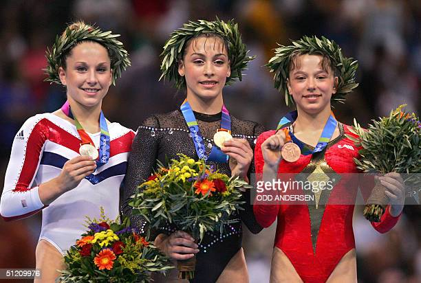 US silver medallist Carly Patterson Romania's gold medallist Catalina Ponor and Romania's bronze medallist Alexandra Georgiana Eremia are seen on the...